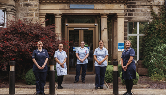 Sue Ryder Wheatfields Hospice staff together at the front entrance