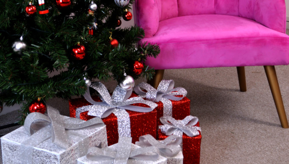 A Christmas tree and presents, next to a pink suede armchair