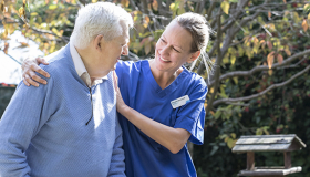 A nurse helping an older gentleman around the garden