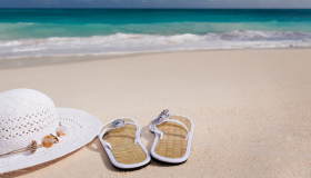 Image of sandals and a sun hat on the beach