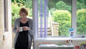 Photo of a woman standing in a doorway holding a cup of tea