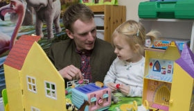 Image of a man and child playing with a toy house