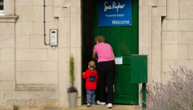 Image of a child and adult walking into Thorpe Hall Hospice