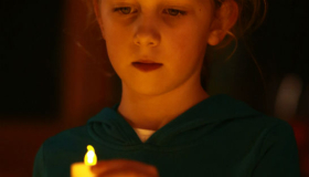 A child lighting a dedication candle at Thorpe Lights of Love