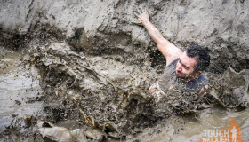 Tough Mudder South West participant jumps in to a mud pool