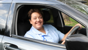 A Leckhampton Hospice at Home nurse driving a car