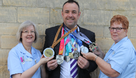 Julian Goodwin alongside Sue Ryder nursing assistants Gerri Garrott and Kathy Dalby with his medal haul from 2018