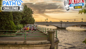 Thames Path Challenge participants walk along the path towards a bridge at sunset