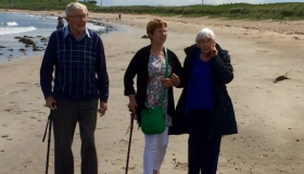 Eileen, Pete and Julia Cook walking on the beach