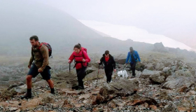 four walkers and a dog navigate past boulders in the mist