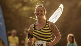 A runner dressed as a bumblebee takes on the Solstice Saunter