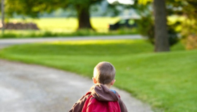 Small child with a backpack walking in the countryside