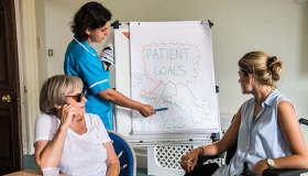 A Sue Ryder Nurse discusses a neurological care plan with a patient and her family