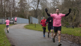 a daily dash runner comes towards the camera with hands raised as if he is cheering. two more runners appear behind him.