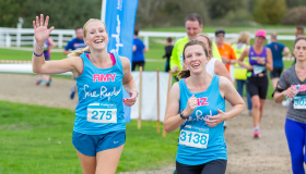 Two Sue Ryder runners pass the Cheerpoint at the Cheltenham Half