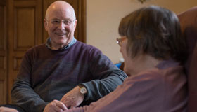 A carer sitting down with the person they are looking after at home