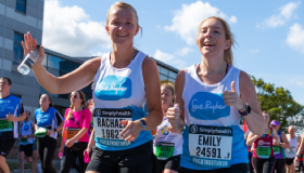 Two Sue Ryder runners smile as they run past