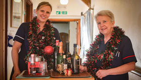 Sue Ryder Nurses with a drinks tray and tinsel