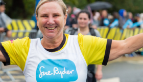 Sue Ryder runner smiles as she passes cheer point
