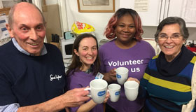 Four volunteers holding Sue Ryder tea cups at our Bury St. Edmunds shop.