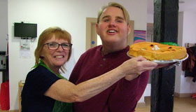 A carer with a young person, holding their new cake creation.
