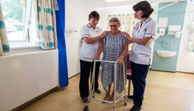 Two Sue Ryder Nurses helping a patient walk