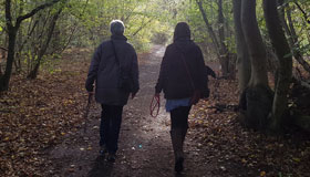 Two people walking in the woods for Walk to Remember 2020