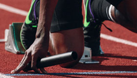 A runner at the starting line with a baton