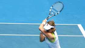A tennis player striking a ball across the court
