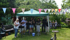 Musicians playing in a tent for Wheatfields Summer Fair.