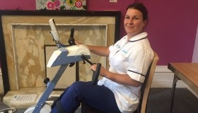 Image of Sue Ryder team member cycling on an exercise bike in her break from work