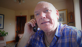 Sue Ryder Leckhampton Court Hospice volunteer befriender Stewart Rood calls a befriendee on the phone.