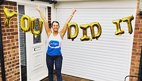 Sarah Riley in her Sue Ryder gear, celebrating with balloons