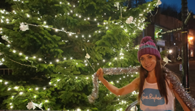 Harriet, in her Sue Ryder running gear, next to a decorated Christmas tree.