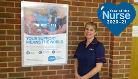 Nurse Helen Andrews standing in front of a Sue Ryder poster