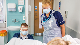 A Sue Ryder doctor and nurse in PPE at a patient's bedside
