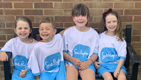 Four young Sue Ryder supporters in Sue Ryder t-shirts